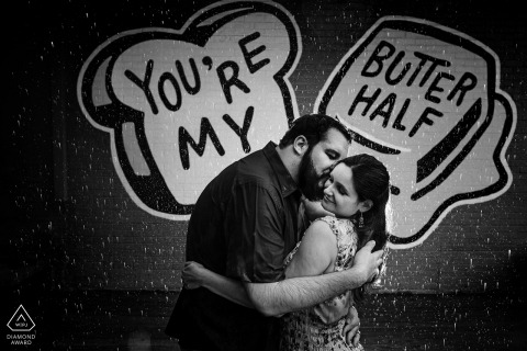 Austin TX engagement portrait of a couple holding each other in front of a mural