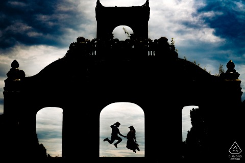 Hue, Vietnam engagement portrait of a silhouetted building and the couple as they jump in the doorway