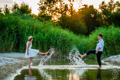 Albena, Bulgaria couple have fun kicking water on each other at the lake.