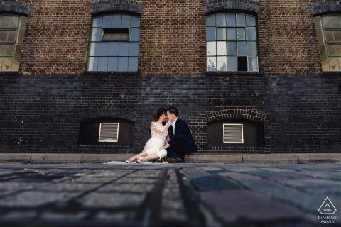 Ein Paar, das auf dem Boden saß und während einer Verlobungssitzung in London aus einem niedrigen Winkel schoss