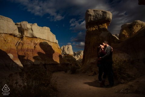The Paint Mines, Calhan Colorado engaged couple smooch in the otherworldly landscape of the paint mines canyon.