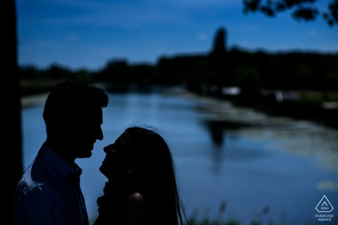 de klinge couple posing for pre-wed portraits at dusk by the water