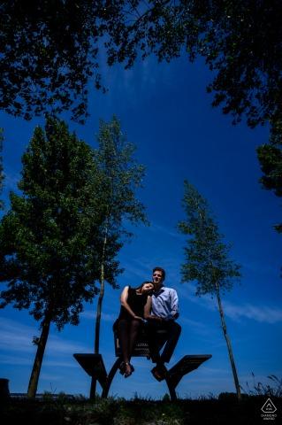 de klinge paar zittend op een bankje en verlicht onder hoge bomen