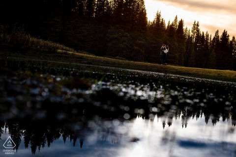 A reflection shot through a pond of water right before the sunset during couple pre-wed portraits in Vail Pass, Vail, CO