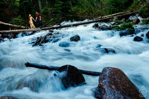 The engaged couple crossing the raging river while balancing on a log during portraits in Frisco, CO