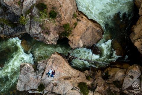 Drohnenbild Blick auf ein Paar, das auf einem Felsen liegt, während der Twin Lakes River unter ihnen in Twin Lakes, CO, tobt