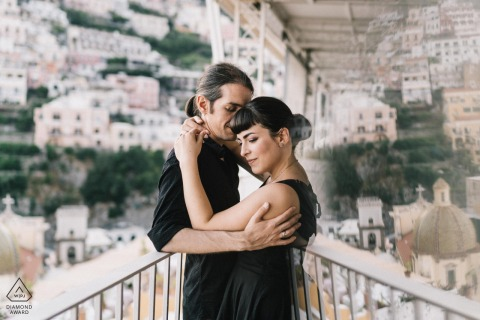 A couple embracing one another on a balcony with homes on a hill in Positano in the background