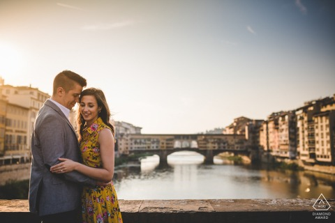 Engagement photo with Ponte Vecchio as background, embracing over the water