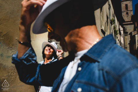 Engagement photo session with a couple wearing hats in Arezzo, a medioeval city in Tuscany