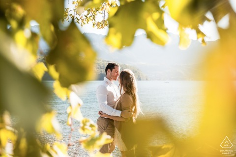 Portrait of a couple at the edge of Lake Annecy, through the leaves in autumn