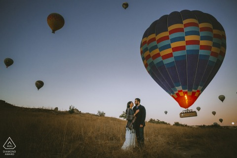 a Turkey couple posing in front of the hot air balloons taking off in Cappadocia