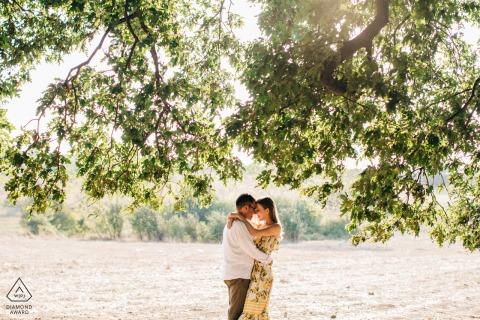 Bursa-Paar heiratete Porträts im Sonnenlicht unter den Ästen
