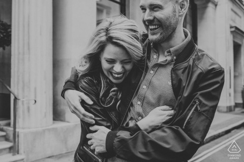 UK Black and white couple engagement shoot in City Of London of a couple laughing in the street
