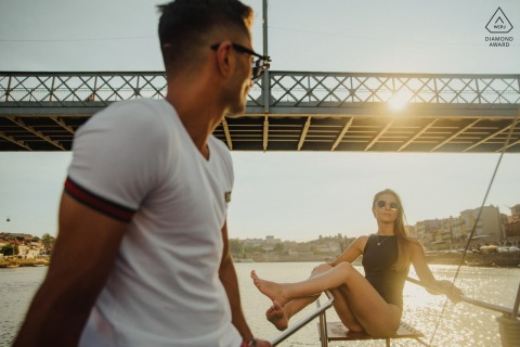 Boating engagement portraits at Oporto - Douro River of the couple ejoying the sunset in a sailboat
