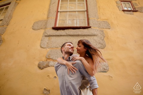 Urban fun couple engagement portrait of piggyback rides in the streets of Porto