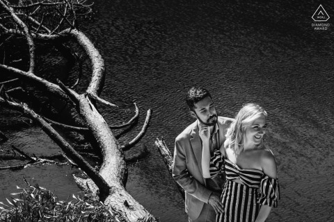 Black and white branches engagement photos of couple having fun near a lake with a dead tree at Sintra, Lisboa, Portugal