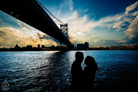 Under the bridge engagement photography of the couple silhouetted against the water while on a boat at sunset in Philadelphia, PA