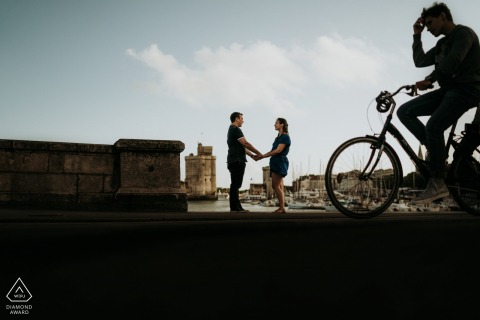 Silhouette bike passing couple engagement photos at La Rochelle, France