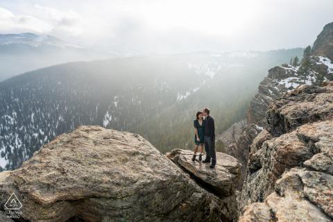 Rocky Mountain Peaks portraits d'engagement de couple à Evergreen, CO avec les montagnes en arrière-plan