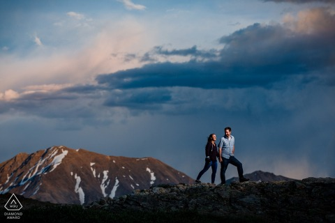 Mountain snow engagement picture session of the couple walking on top of Independence Pass as the sun sets in Colorado