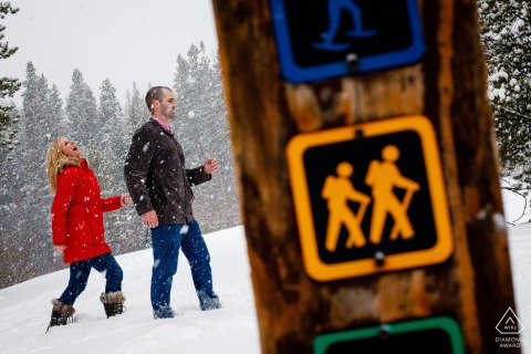 Winter snow hiking couple engagement image from Breckenridge, CO next to hiking signs