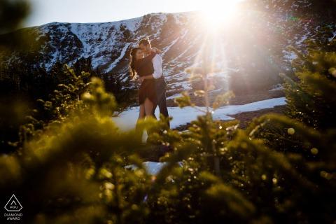 Verlobungsporträts von Berg-Sunburst-Paaren am Loveland Pass, CO, die Sonne flackert die Linse auf, als sie schnell hinter dem Kamm verschwindet