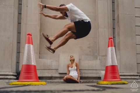 England verspielte Straßen-Verlobungsfotografie in London des Bräutigams, der über Braut springt