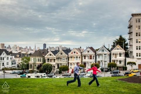 Séance photo d'engagement de N. CA à San Francisco d'un couple qui traverse le green devant les Painted Ladies