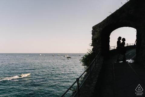 E-sessie van een paar gesilhouetteerd en omlijst in overwelfde galerij door het water in positano
