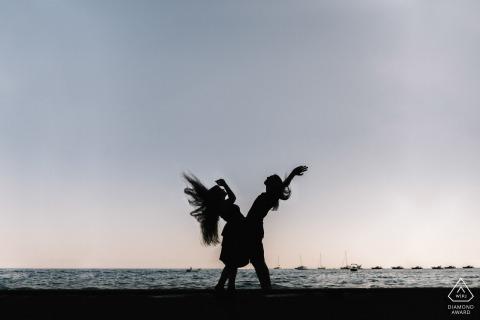 Retratos de pareja de Positano con cabello volando en el cielo