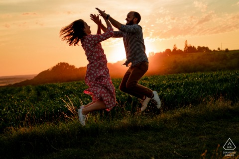 Fun engaged couple portrait at sunset as they jump and high-ten