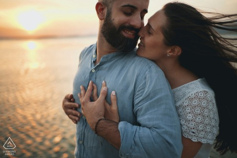 Trasimeno Lake pre wedding photos of the couple embracing at sunset by the water with the wind blowing
