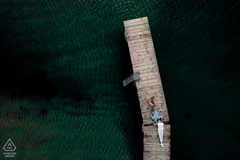 Trasimeno Lake Drone photography engagement session with the couple lying on the wooden dock
