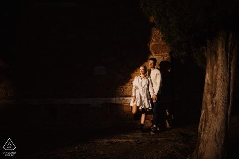 Vitaleta e-session of couple close to the wall in a spotlight of sun