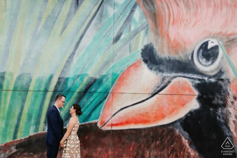 Engagement shoot in Miami Design District, FL  in front of a mural of a cardinal bird