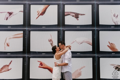 Engagement shoot in Miami Design District, FL of couple standing in front of a wall of panels with artwork of pointing hands