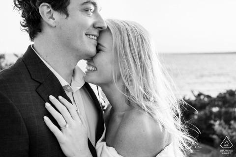 Castle Hill Lighthouse, Newport, RI pareja abrazó posando para su sesión de compromiso en blanco y negro
