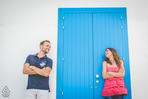 portopalo of capopassero love in sicily engagement portrait shoot against a white wall with a blue door