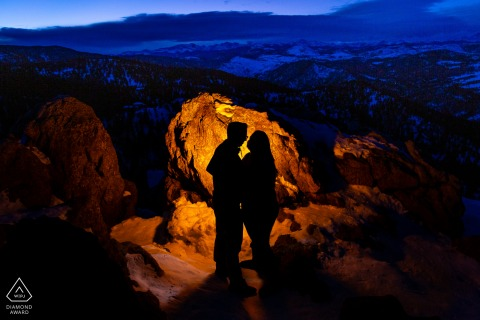 Twilight falls over the mountain view while engaged couple form a silhouette at Lost Gulch, boulder, Colorado