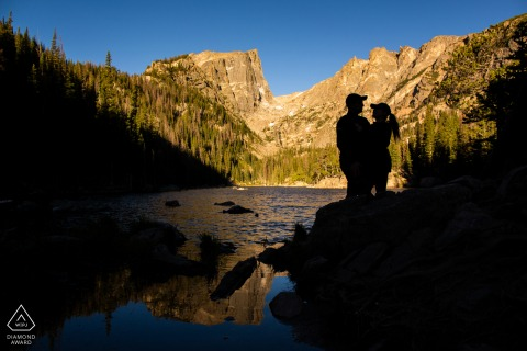 Dream Lake, Rocky Mountain National Park, Coloradocouple rock matching baseball caps on their hiking engagement portrait session