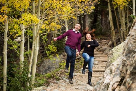 Una coppia di un parco nazionale delle montagne rocciose, Estes Park, Colorado prende sul serio il divertimento mentre salta lungo un sentiero escursionistico per i loro ritratti di fidanzamento