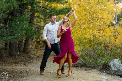 Markleeville, CA Paar tanzt in den Bäumen während ihrer Verlobungssitzung in den Herbstfarben