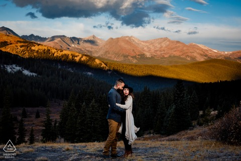 A Breckenridge, CO couple posing for engagement pictures with the First touch of light on the mountain