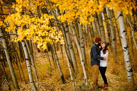 Ehepaar aus Breckenridge, CO, das während seines Verlobungsporträts in den Bergen Witze in einem Feld aus goldenen Blättern teilt