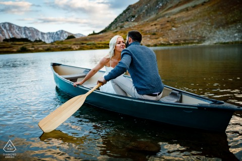 Keystone, CO couple Floating together in a small canoe with paddles on the water