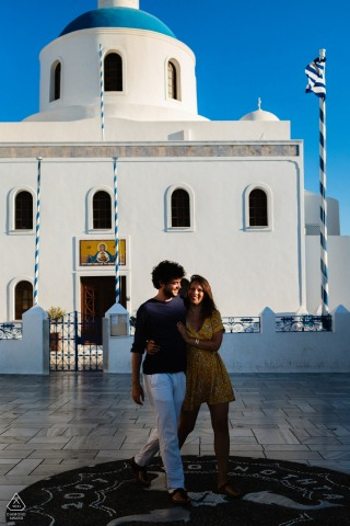 A Santorini Couple walking in front of a church that is white and blue with a blue sky