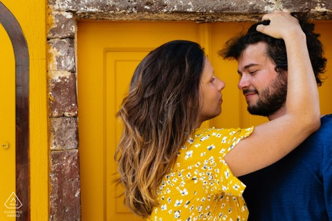 Santorini Couple in front of a yellow door with her yellow dress during their engagement portrait shoot