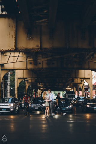 Wabash Ave in Chicago, IL couple is Stopping traffic during their engagement shoot at night with wet urban streets