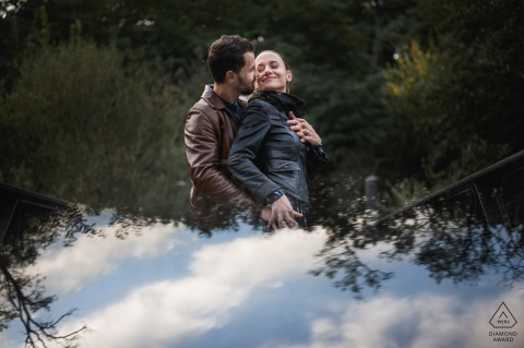 Engagement photo from Nérac, France with reflected clouds below the couple