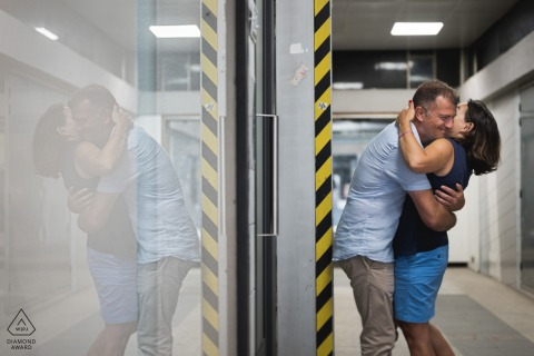 Pre wedding photography from Agen, France of a couple kissing underground with caution tape on the walls with a glass reflection